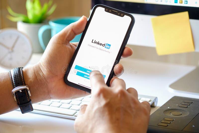 CHIANG MAI, TAILÂNDIA 5 DE MARÇO DE 2018: Homem de negócios que guarda um iPhone X com serviço de rede social LinkedIn na tela iP fotografia de stock royalty free