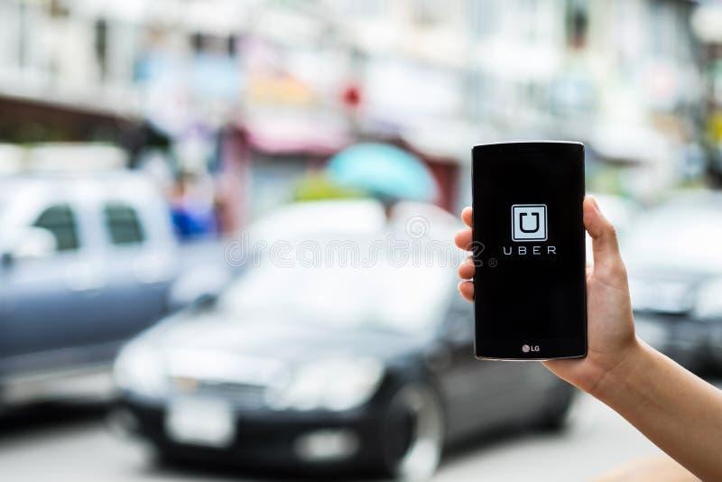 CHIANG MAI TAJLANDIA, LIPIEC, - 17, 2016: Mężczyzna ręka trzyma Uber app pokazuje na LG G4 na drogowym i czerwonym samochodzie, U fotografia stock