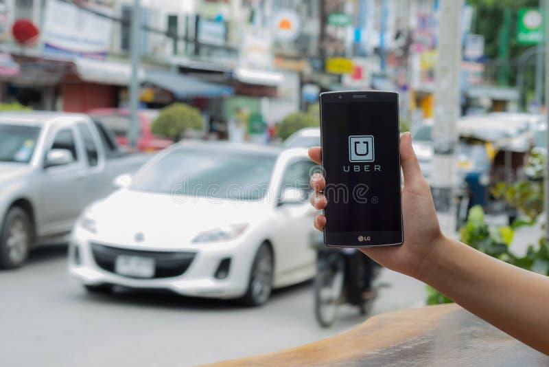 CHIANG MAI TAJLANDIA, LIPIEC, - 17, 2016: Mężczyzna ręka trzyma Uber app pokazuje na LG G4 na drogowym i czerwonym samochodzie, U obraz stock