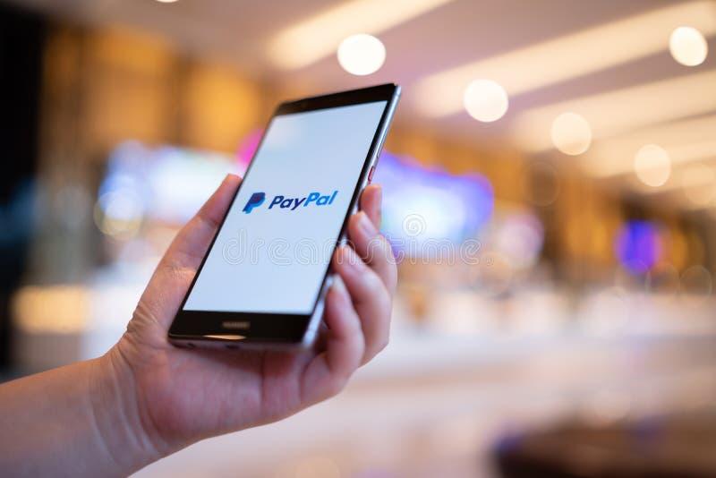 CHIANG MAI TAJLANDIA, Sierpień, - 03,2018: Kobieta wręcza trzymać HUAWEI z Paypal apps na ekranie Paypal jest online elektroniczn fotografia royalty free