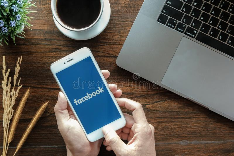 Chiang Mai Tajlandia Stycze? 20, 2019 Samiec trzyma Jabłczanego iPhone 6S z facebook zastosowaniem na ekranie facebook jest fotog zdjęcie royalty free