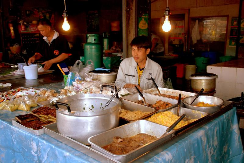 Chiang Mai, TH: Thai Restaurant Food. Two workers with delicious Thai foods displayed in large metal trays and cauldrons at a restaurant in the old city of stock images