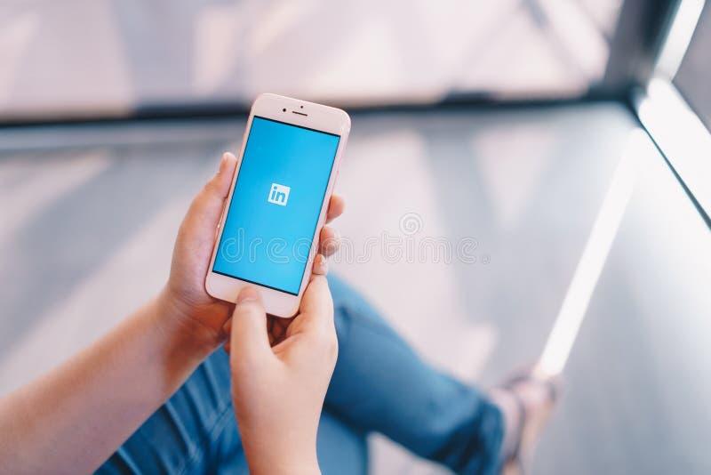 CHIANG MAI THAILAND - April 08,2019: Kvinna som rymmer Apple iPhone 6S Rose Gold med den Linkedin applikationen p? sk?rmen arkivbild