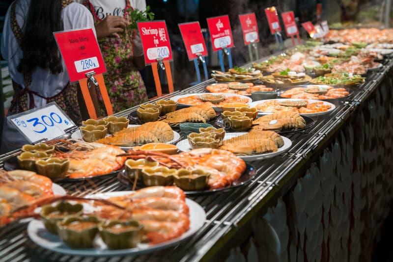 CHIANG MAI THAILAND - CIRCA AUGUSTI 2015: Det lokala folket säljer traditionell thailändsk mat, och drinkar på natten marknadsför royaltyfria bilder