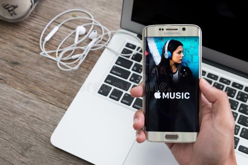 CHIANG MAI, THAILAND - 1 DEC, 2015: Het de holdingsscherm van de mensenhand van Apple-muziek app wordt geschoten die op de melkwe stock afbeelding