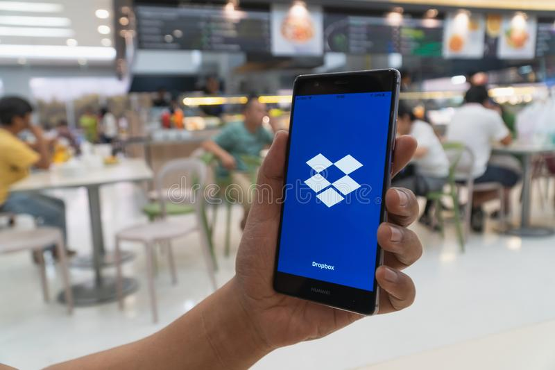 CHIANG MAI, THAILAND - JAN. 06,2019: Man holding HUAWEI with Dropbox on screen. Dropbox is a service that gives you access to. Images, documents and videos royalty free stock image