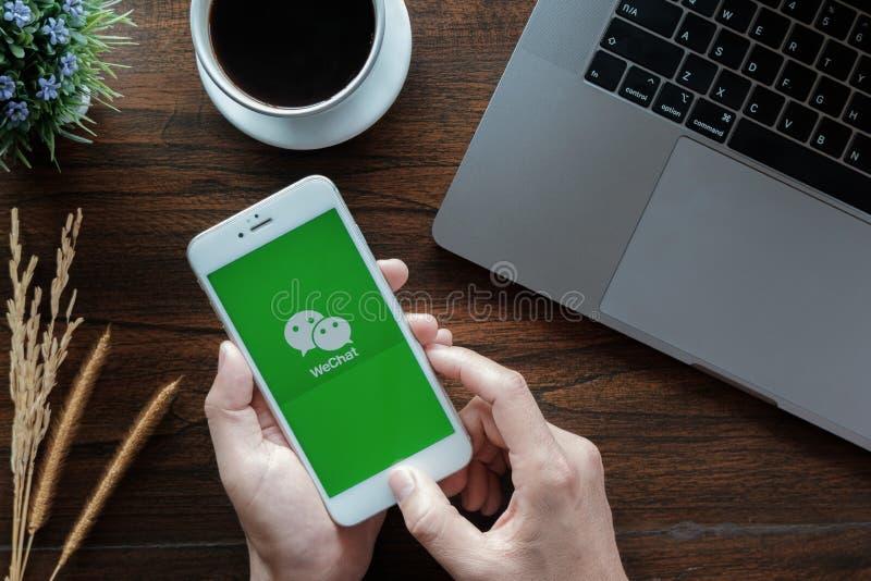 CHIANG MAI THAILAND - Januari 20, 2019: Mannen rymmer iphone 6 med den WeChat appen på skärmen WeChat ?r ett kinesiskt som kan an arkivfoton