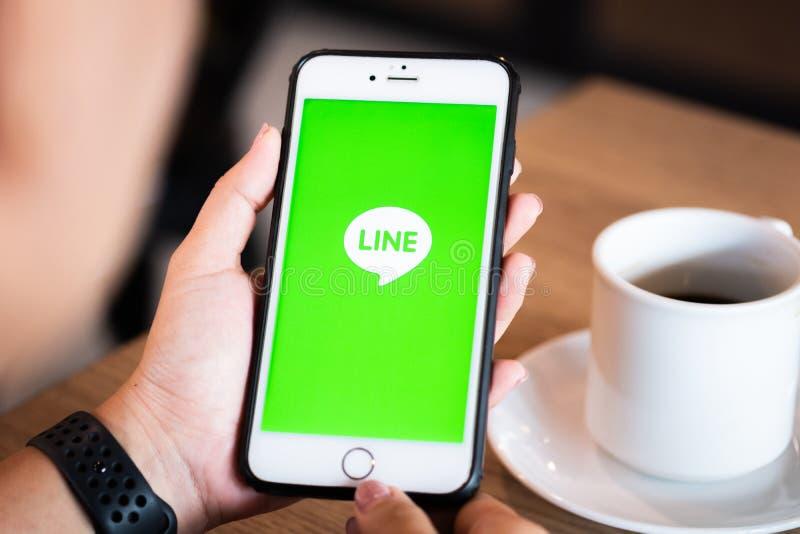 Chiang Mai/Thailand - Juni 22 2019: Händer som rymmer mobilen med linjen skärm i coffee shop arkivfoto