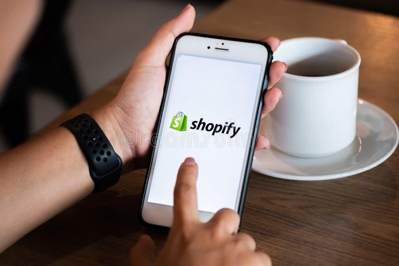 Chiang Mai/Thailand - Juni 22 2019: Händer som rymmer mobilen med, shopify skärmen i coffee shop royaltyfri bild