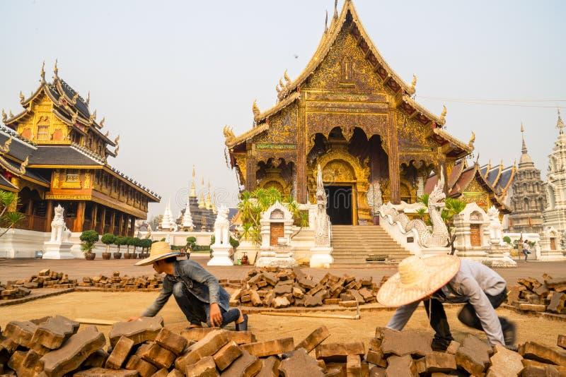 Chiang Mai /Thailand - 16 Maart, 2019: De arbeider bedekt de gang met keien in een Boeddhistische tempel royalty-vrije stock afbeeldingen
