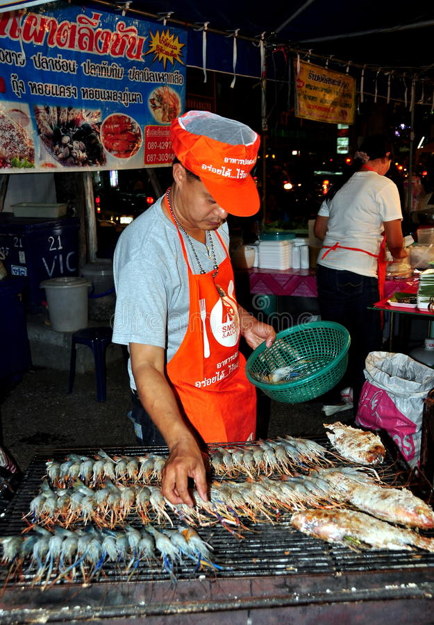 Chiang Mai, Thailand: Man Grilling Squids. Cook grilling fresh squids on a barbecue at the Tha Phae Square New Year's Festival in Chiang Mai, Thailand royalty free stock photos