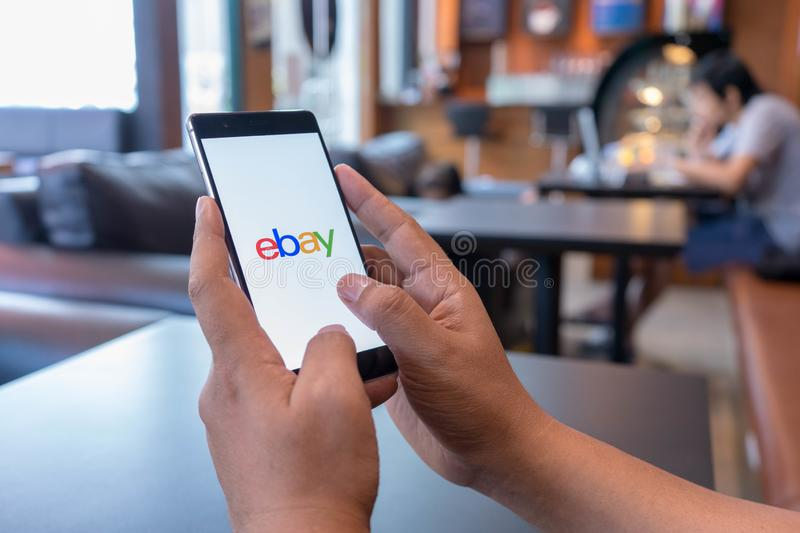 CHIANG MAI, THAILAND - Mar 18,2018: Man holding HUAWEI wit. H eBay apps on the screen. eBay is one of the most popular ways to buy and sell goods and services on stock photo