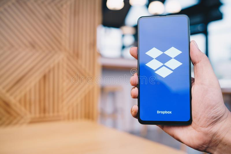CHIANG MAI, THAILAND - Mar. 23,2019: Man holding Xiaomi Mi Mix 3 with Dropbox on screen.Dropbox is a service that gives you access. To images, documents and stock photos