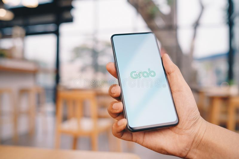 CHIANG MAI, THAILAND - Mar. 23,2019: Man holding Xiaomi Mi Mix 3 with Grab apps on screen. Grab is smartphone app all-in-one. Transport booking in South-East stock images