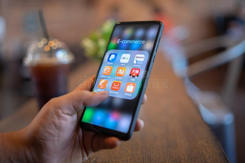 CHIANG MAI, THAILAND - Mar. 24,2019: Man holding Xiaomi Mi Mix 3 with icons of E-commerce and online shopping on screen.smartphone. Lifestyle,e-commerce app stock photo