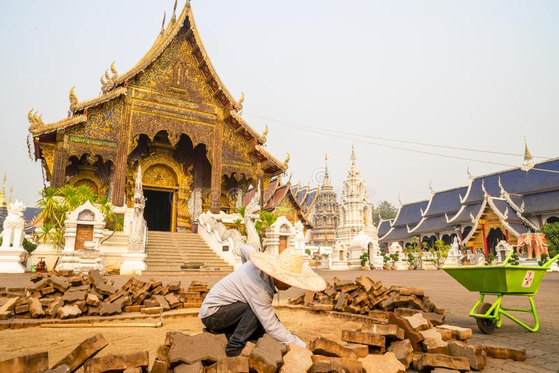 Chiang Mai /Thailand - mars 16, 2019: Arbetaren stenl?gger g?ngbanan med kullersten i en buddistisk tempel arkivfoto