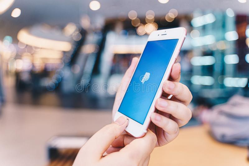 CHIANG MAI THAILAND - MAY 10,2019: Kvinna som rymmer Apple iPhone 6S Rose Gold med Paypal apps på skärmen arkivfoto