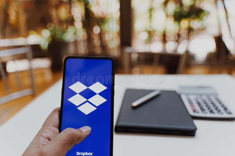 CHIANG MAI, THAILAND - May.26,2019: Man holding Xiaomi Mi Mix 3 with Dropbox on screen.Dropbox is a service that gives you access. To images, documents and royalty free stock image