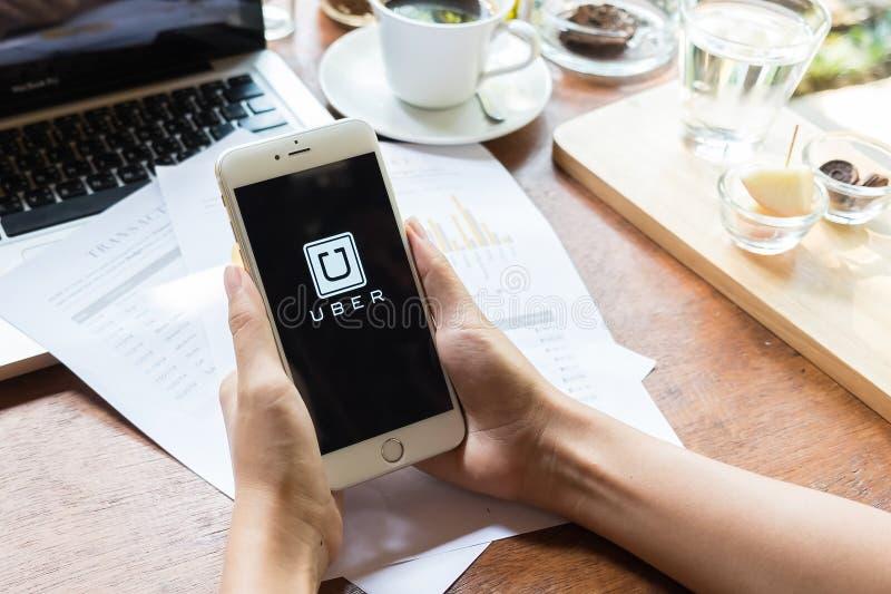 CHIANG MAI, THAILAND - MEI 09.2015: Een holding Uber die app van de vrouwenhand op iphone 6 plus in koffiewinkel tonen, Uber is s stock fotografie