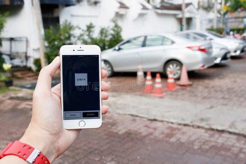 CHIANG MAI, THAILAND-SEP 02,2016: Una mano de la mujer que sostiene el appli de Uber imagen de archivo