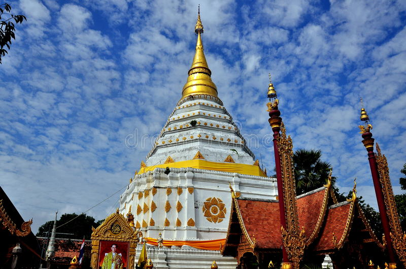 Chiang Mai, Thailand: Wat Chang Yuen. A photograph of King Bumibhol stands in front of the immense stepped white Chedi capped by a gilded spire dominates Wat royalty free stock photo