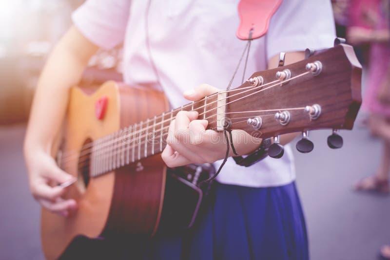 Chiang Mai Walking Street, Vinger Meisjes in school eenvormig Wit overhemd, blauwe rok, gitaarspeler stock foto