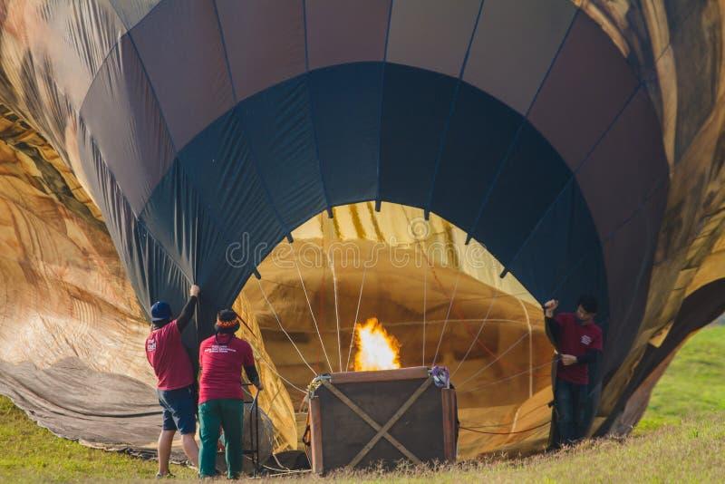 Chiang Rai, Tailândia - em fevereiro de 2019: O pessoal está fundindo o ar quente no balão de modo que o balão com a raça foto de stock