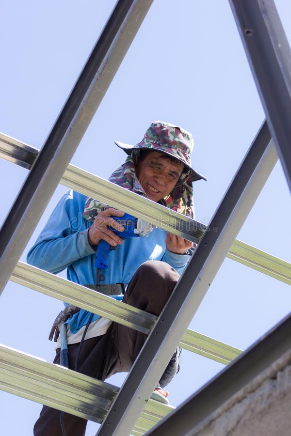 CHIANG RAI, THAILAND - AUGUST 20 : close-up unidentified male roofer working on the roof on August 20, 2018 in stock images