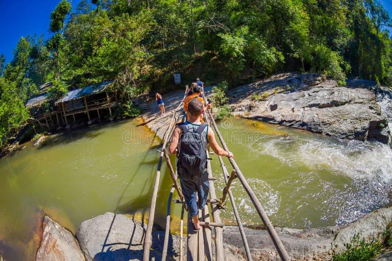CHIANG RAI THAILAND - FEBRUARI 01, 2018: Oidentifierat folk som använder en träbro för att korsa över en liten flod in royaltyfria bilder