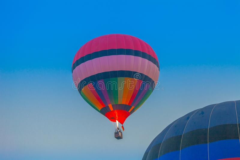 Hot air balloon flying in the sky at sunrise. Chiang Rai,Thailand - February 18,2018:hot air balloon flying above Singha park in Chiangrai Thailand. balloons stock images
