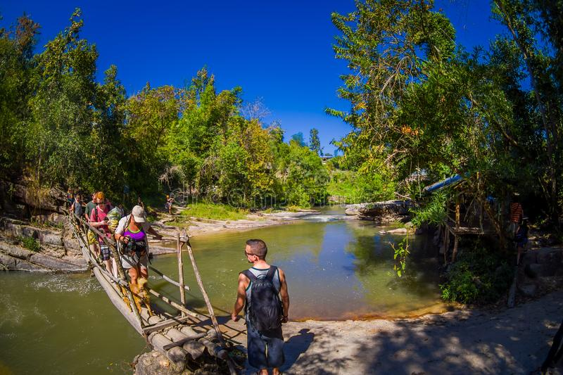 CHIANG RAI, THAILAND - FEBRUARY 01, 2018: Outdoor view of unidentified people walking in tropical rainforest using a. Wooden bridge over a small river in Chiang stock photography