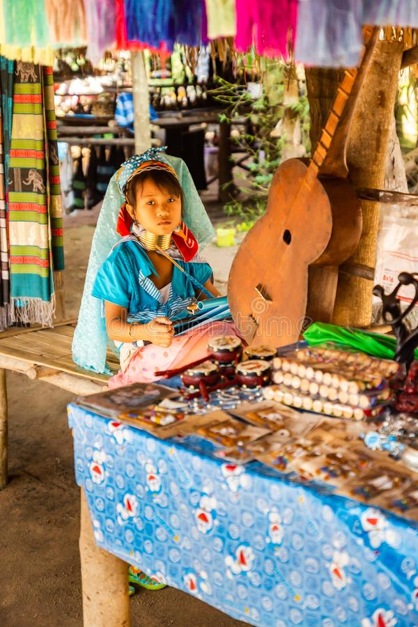 A little girl with a long neck and rings on her making silk in long neck village stock photography