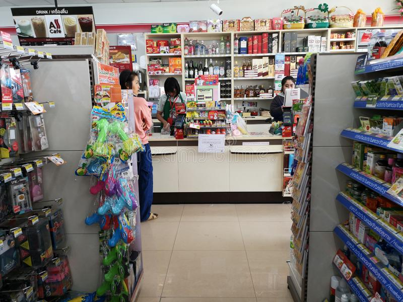 CHIANG RAI, THAILAND - JANUARY 10 : unidentified woman paying money at cashier in 7-eleven store on January 10, 2019 in Chiang rai royalty free stock photography