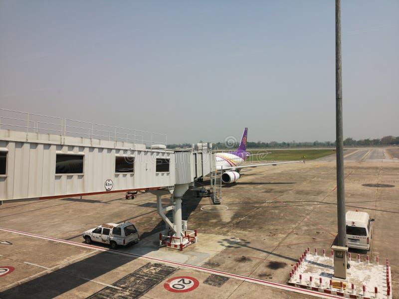 CHIANG RAI, THAILAND - MAART 29: aerobrug of het jetway verbinden met het vliegtuig bij luchthaven op 29 Maart, 2019 in Chiang-ra stock afbeelding