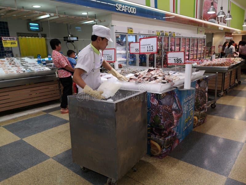 CHIANG RAI, THAILAND - MAART 4: De niet geïdentificeerde Aziatische mens met witte hoed bracht aan ijs op verse zeevruchten in su stock afbeeldingen