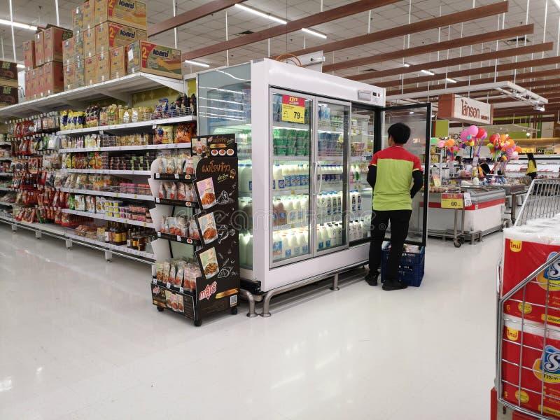 CHIANG RAI, THAILAND - MAART 4: Niet geïdentificeerde Aziatische mannelijke arbeider die goederen op koelkast in supermarkt op 4  stock foto