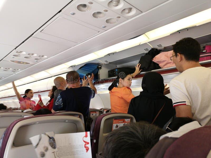 CHIANG RAI, THAILAND - MAART 29: niet geïdentificeerde steward die de Aziatische bagage van de mensenplaats in luchtcompartiment stock afbeeldingen