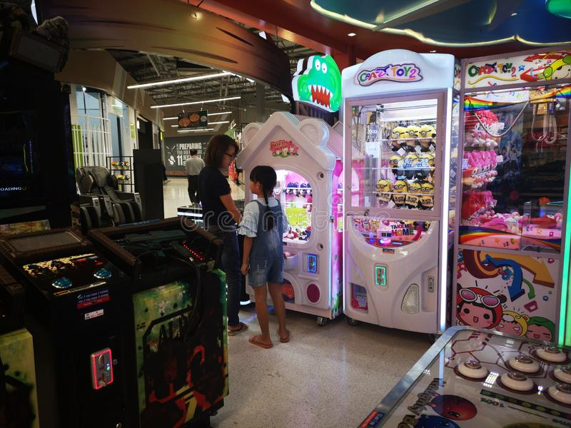 CHIANG RAI, THAILAND - MARCH 7, 2019 : unidentified woman and girl playng catching dolls at arcade game and entertainment zone in stock image