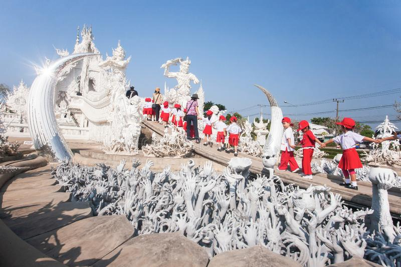 A group of elementary schoolchildren holding hands while walking to the White Temple. Wat Rong Khun, Thailand stock photo