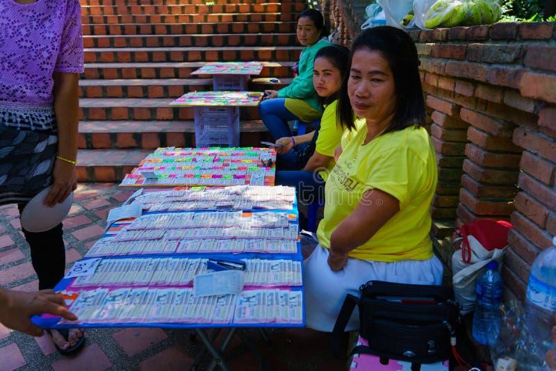 Chiangmai, Таиланд - 13-ое октября 2018: Тайские люди с инвалидностью продают билеты лотереи к людям которые прошли мимо для того стоковое изображение rf