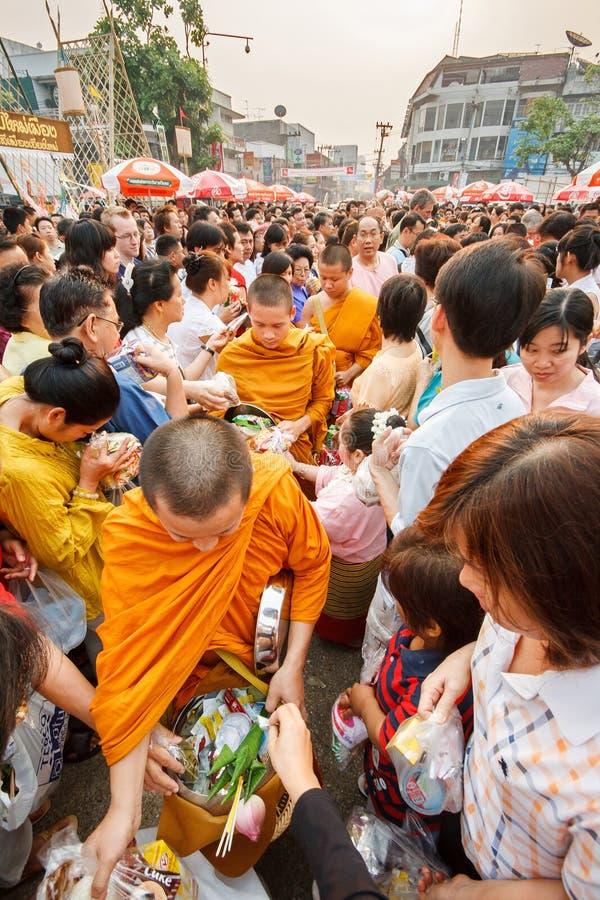 CHIANGMAI - 13 DE ABRIL DE 2008: El festival de Songkran, gente puso ofrendas de la comida en las limosnas de un monje budista ru fotografía de archivo libre de regalías