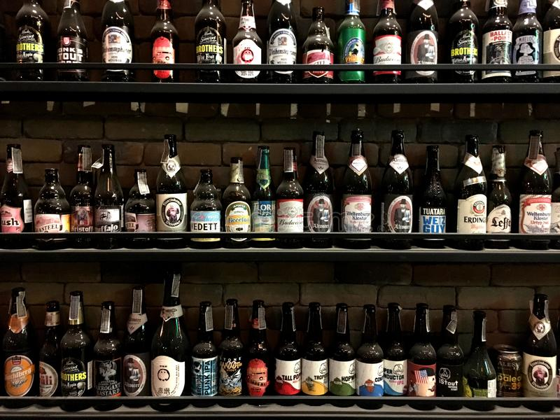 CHIANGMAI, TAILÂNDIA - 3 DE JANEIRO DE 2019: Decoração mundial da garrafa de cerveja do tipo na prateleira na frente da parede de imagem de stock