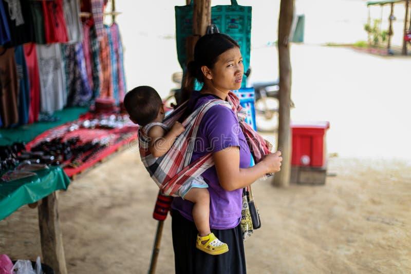 Chiangmai, Tailandia - 31 de marzo de 2016: La madre lleva a su pequeño hijo en el distrito del sabor de Mae de Chiang Mai Thaila fotografía de archivo libre de regalías