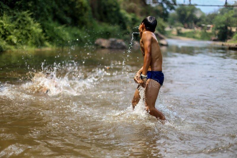 Chiangmai, Tailandia - 31 marzo 2016: Un ragazzo sta divertendosi saltando l'acqua nel clima caldo immagine stock libera da diritti