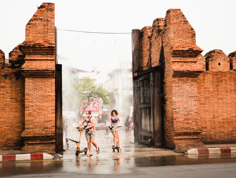 CHIANGMAI,THAILAND APRIL 9,2019 -Travellers ride mini electric scooter at Thapae gate Ancient brick wall of Chiangmai royalty free stock photo