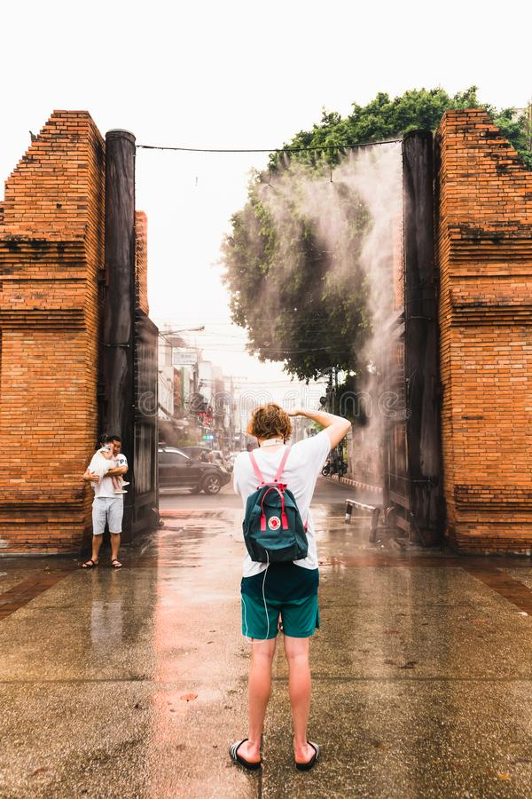 CHIANGMAI,THAILAND APRIL 9,2019 - Young European Tourist taking a photo at Thapae gate ancient brick wall of Chiangmai with water royalty free stock photo