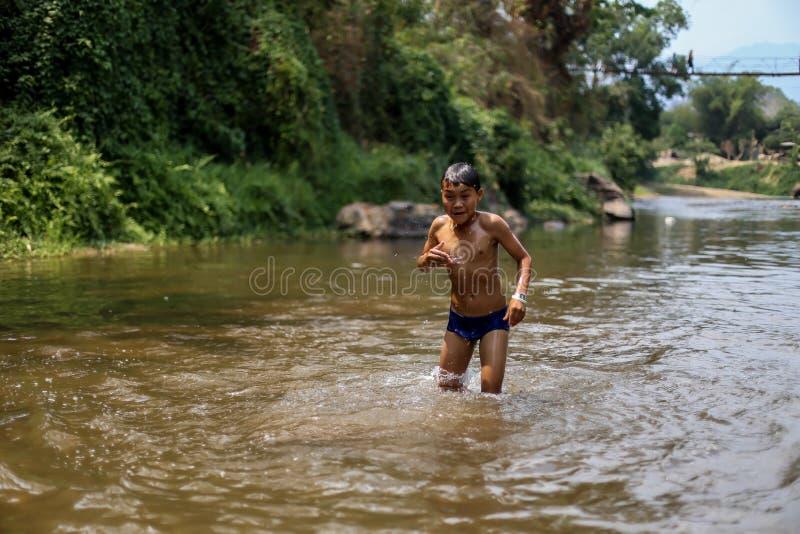 Chiangmai, Thailand - Maart 31, 2016: Chiangmai, Thailand - Maart 31, 2016: Een jongen is Bamboe het rafting in het wildernisnoor stock foto