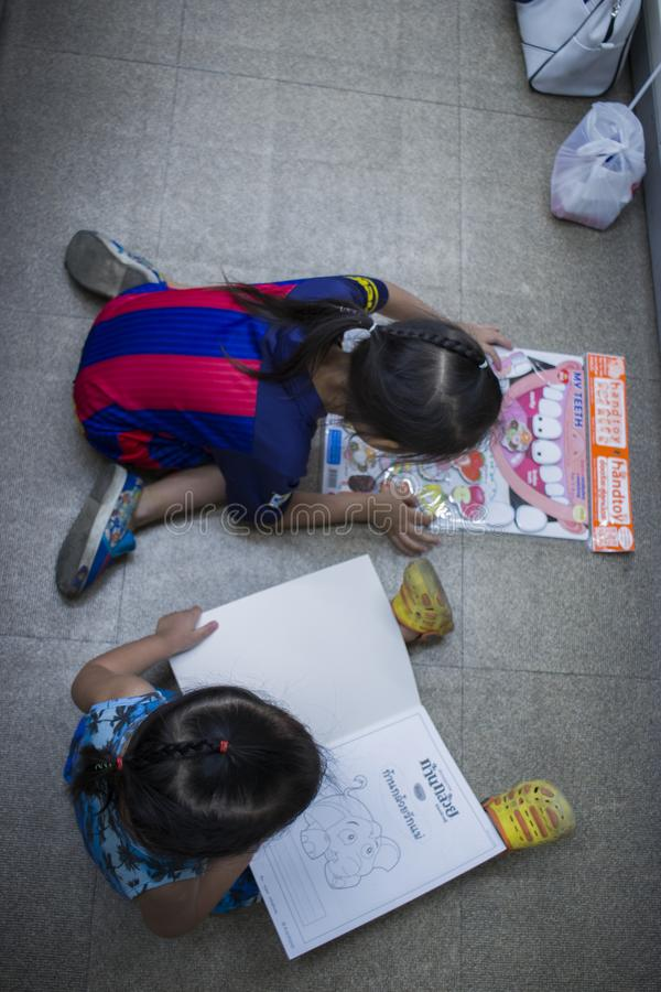 CHIANGMAI, THAILAND-MAY 3,2019: маленький ребенок 2 исследует и читающ книгу во взгляде сверху книжного магазина стоковая фотография rf