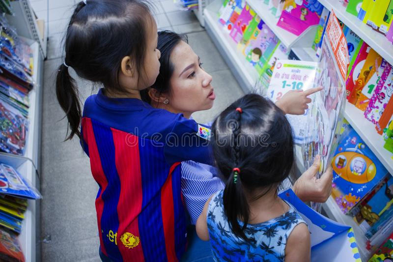CHIANGMAI THAILAND-MAY 3,2019: Det lilla barnet unders?ker bokhyllorna med mamman i boklager royaltyfri fotografi