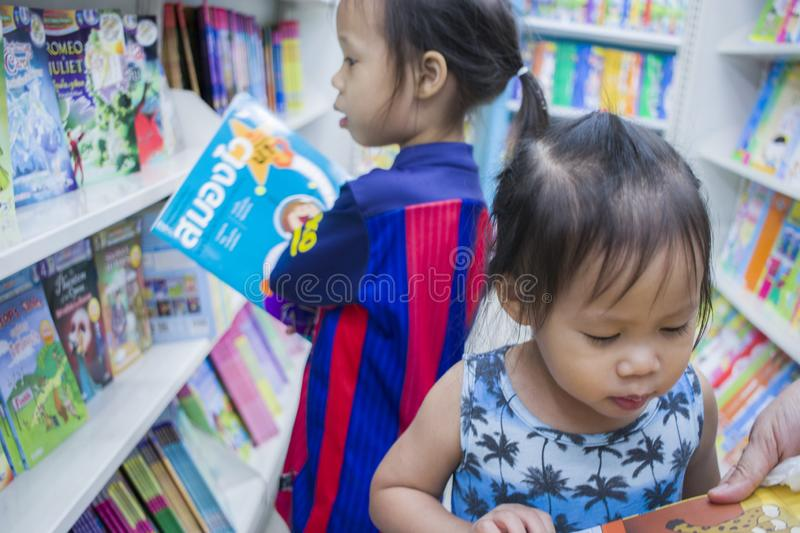 CHIANGMAI,THAILAND-MAY 3,2019 : Little Child explores the bookshelves with mom in book store royalty free stock photo